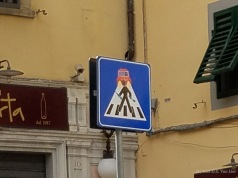 A street sign with decals by Clet Abraham (Florence)