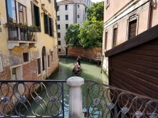 A gondola makes its way through a Venice canal.
