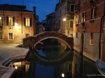 A nighttime view of a bridge across a Venice canal.